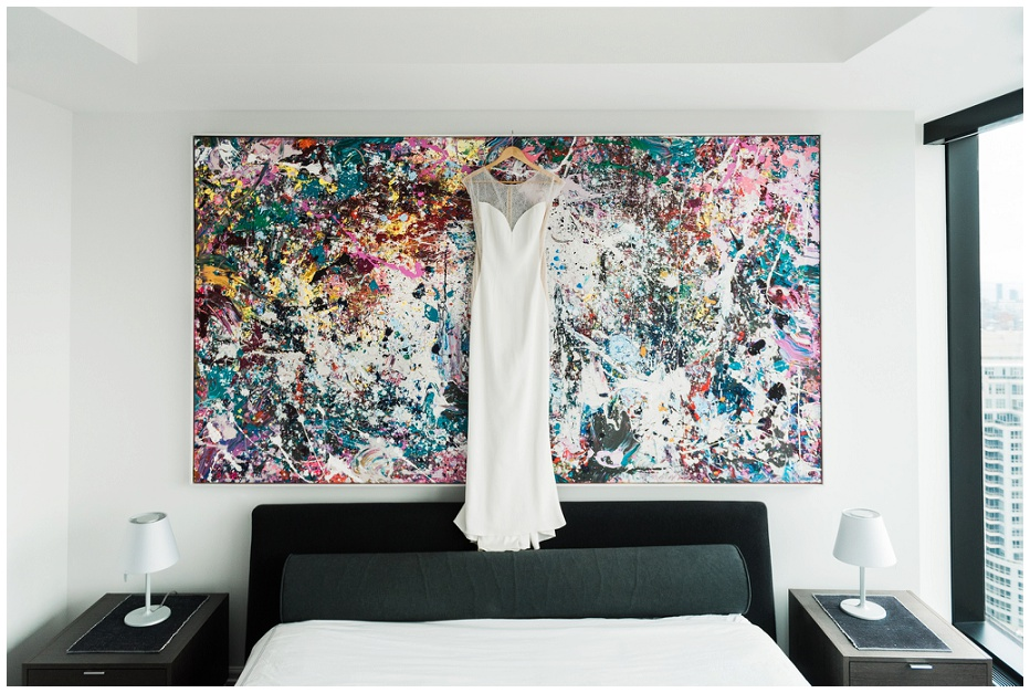 Modern wedding dress hanging from a piece of colourful splattered art in Toronto at Four Seasons Hotel Private Residences