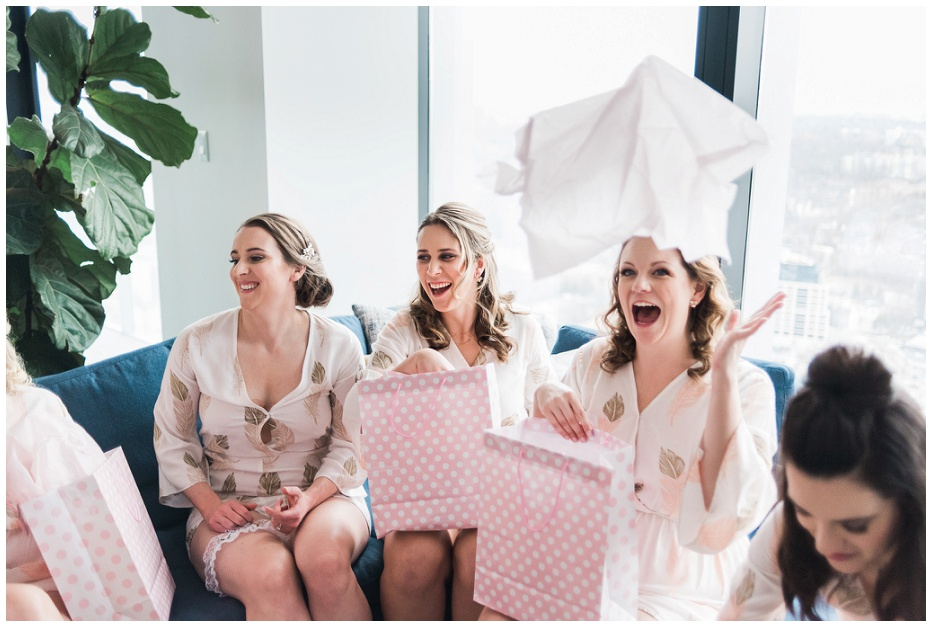 Bridesmaids opening their pink gift bags from Toronto bride and throwing the tissue paper in the air at Four Seasons Hotel wedding photos