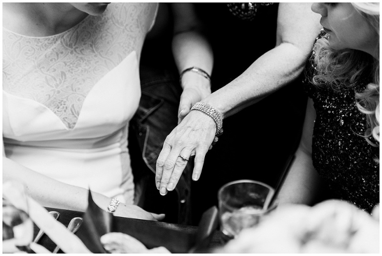 Mother of the bride showing her daughters her wedding ring at jump restaurant