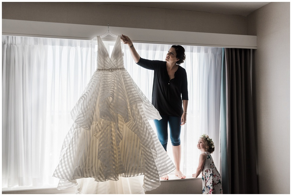 Bride picking up wedding dress while her daughter looks up at her before Kurtz Orchard wedding