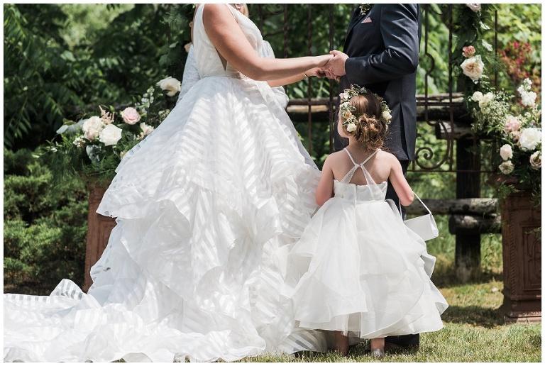 Bride & Groom's daughter hugging dad's leg during ceremony at Kurtz Orchards