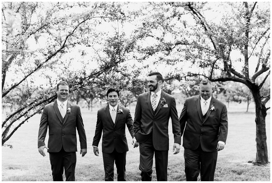 Groomsmen walking through orchard at Kurtz Orchard wedding