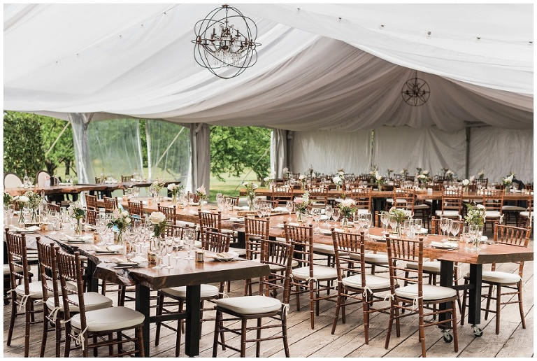 Wooden chairs at live edge tables decorated inside white tent at Kurtz Orchard wedding
