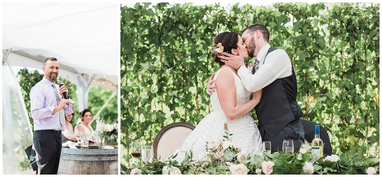 Bride and groom kissing at head table in from of greenery wall at Kurtz Orchard wedding