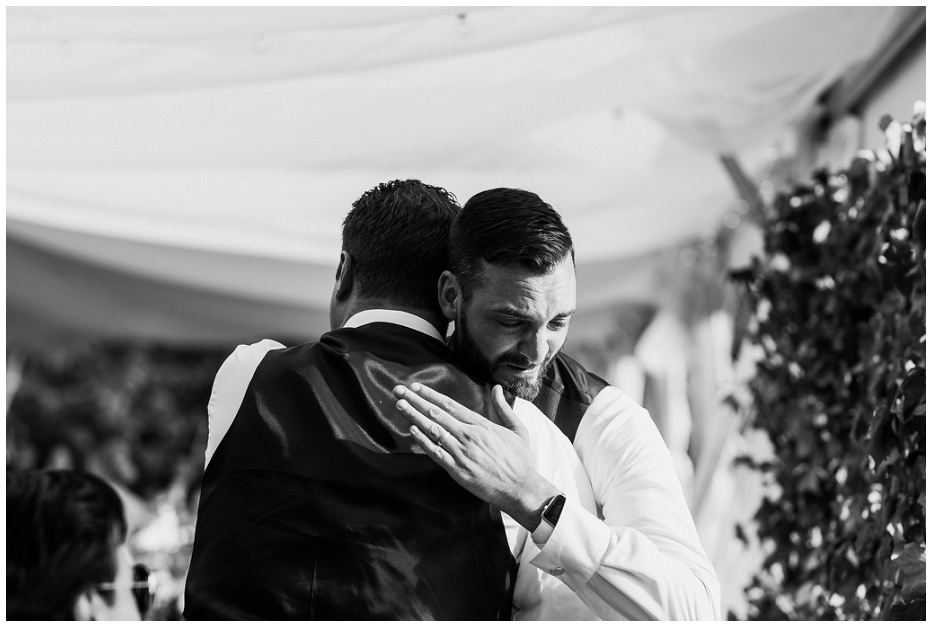 Groom hugging groomsman and almost crying at Kurtz Orchard wedding