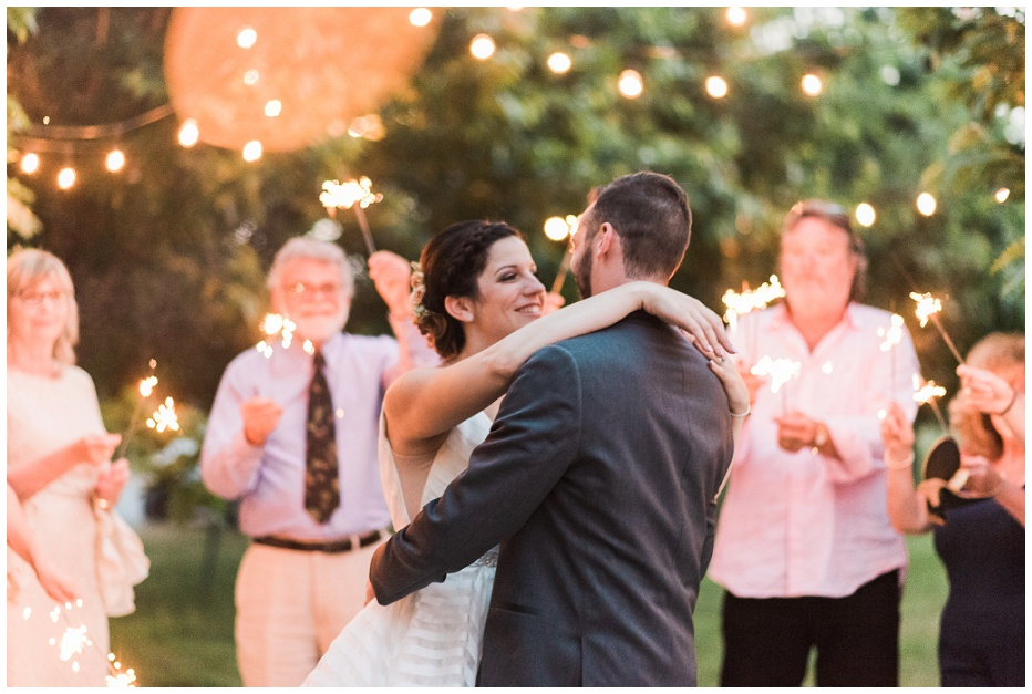 Bride and groom dancing at dusk with guests holding sparklers in background at Kurtz Orchard wedding