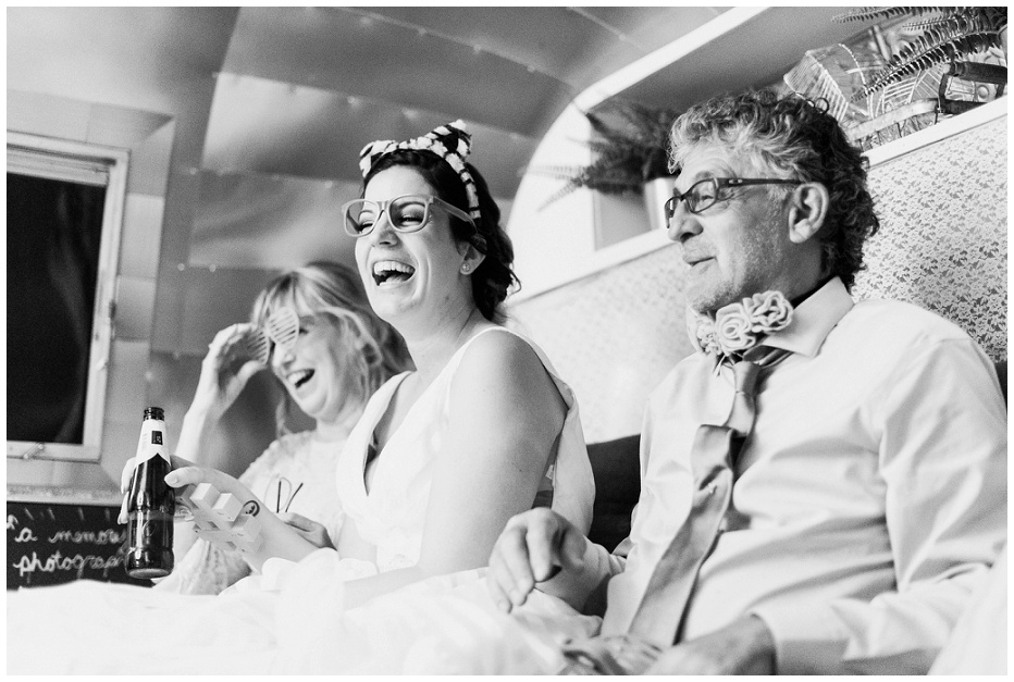 Bride inside airstream photobooth laughing with parents at Kurtz Orchard wedding