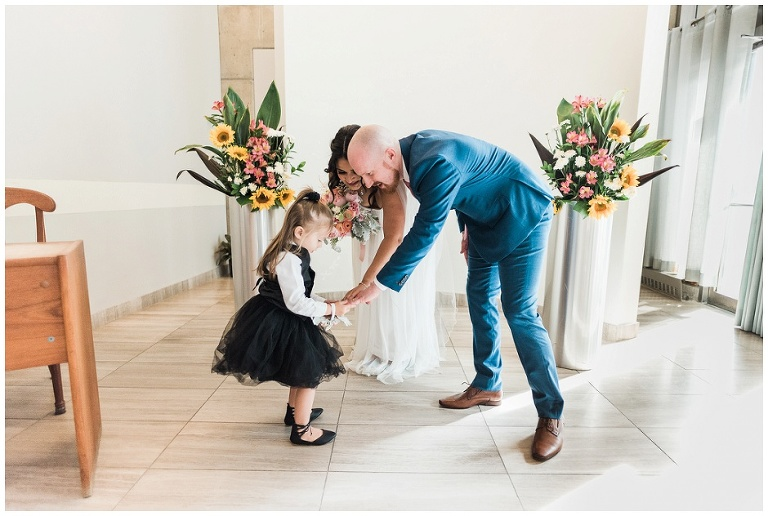Bride and groom's young daughter holding parents hands, asking to see their wedding rings together