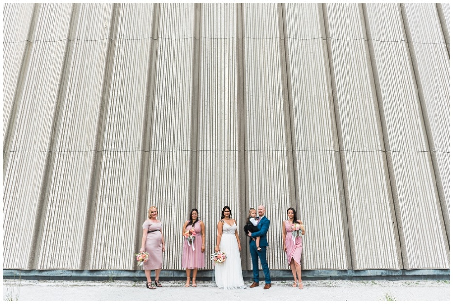 Wedding party in pink dresses standing outside Toronto City hall walls