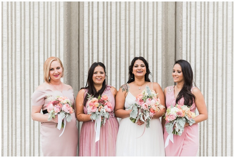 Bridal party laughing together in pink dresses with their Dereves Floral bouquets
