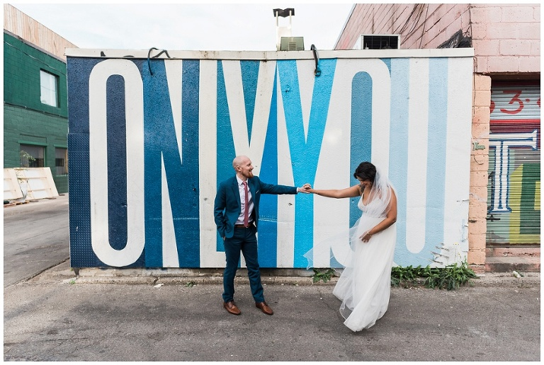 Bride and groom standing in front of graffiti that says Only You on Ossington strip by Ben Johnston