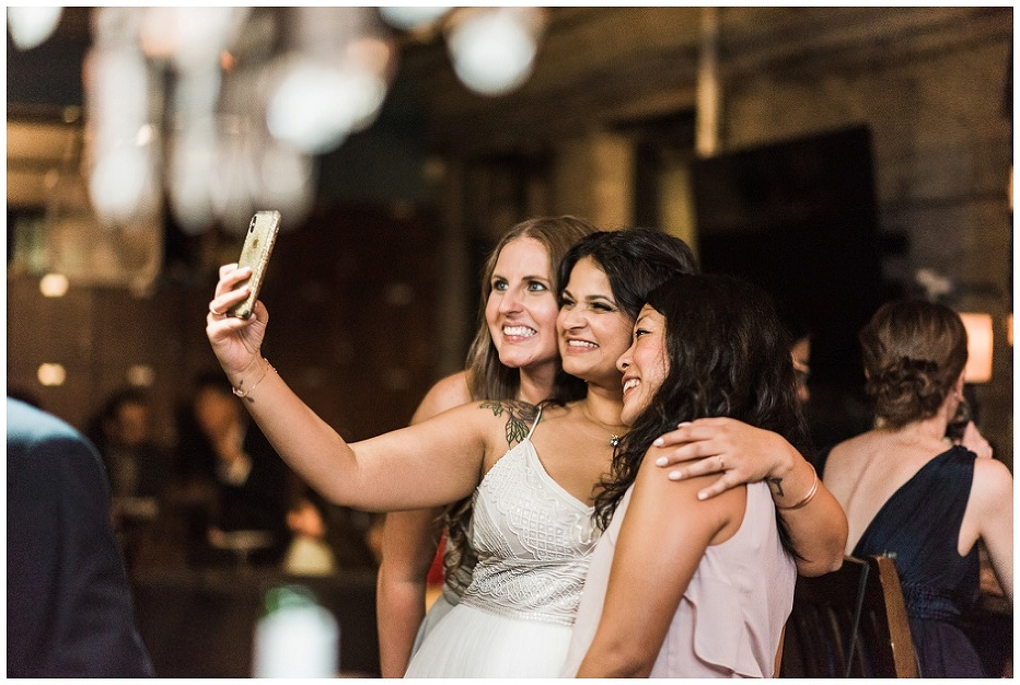 Bride takes a selfie with friends at The Lodge on Queen