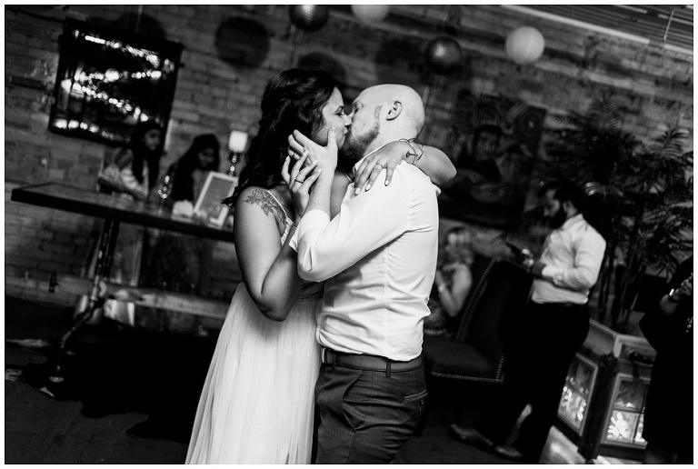 Groom grabbing brides face with hands to kiss her during their first dance at The Lodge on Queen