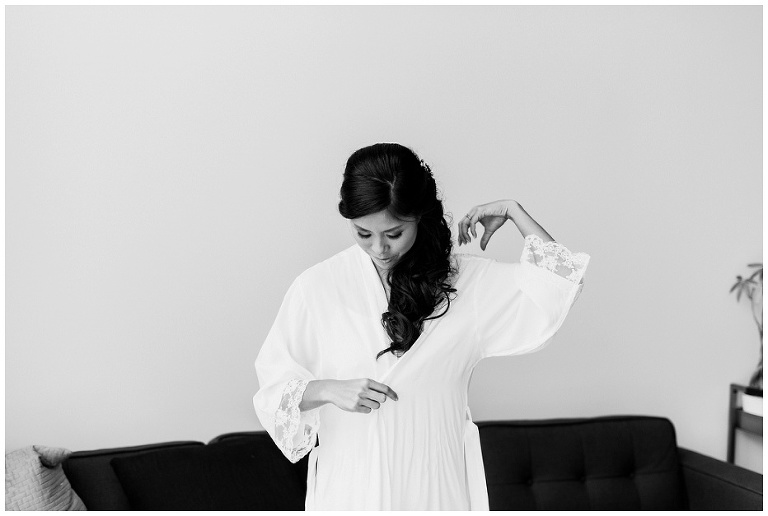 Black and white photo of bride putting on white robe