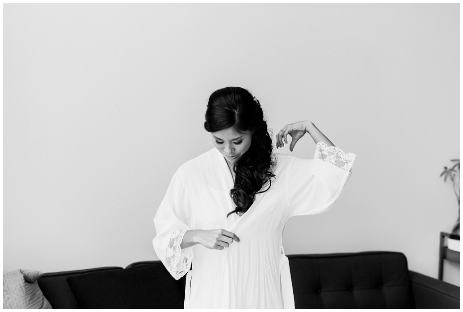 Black and white photo of bride putting on white robe
