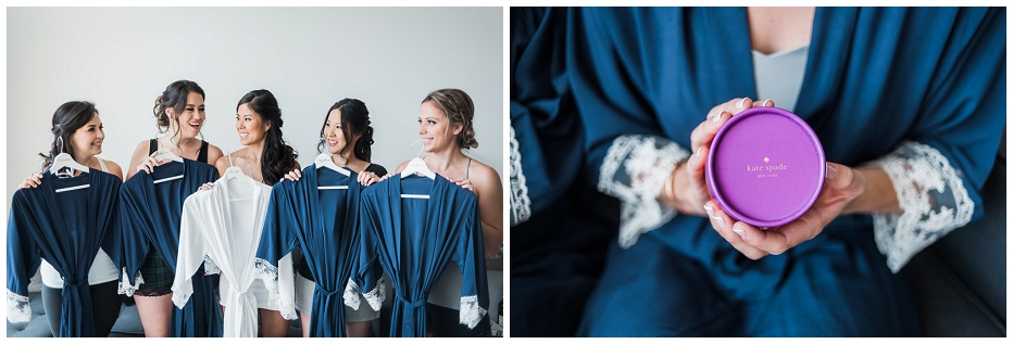 Bridesmaids holding their navy robes up and looking at each other