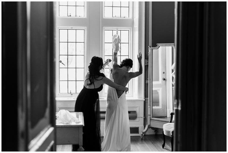 Looking through the door of bridal suite, bridesmaid helps bride put on wedding dress