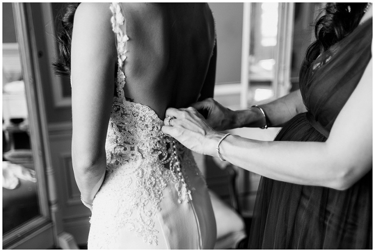 Black and white close up of bride's sister buttoning up bride's wedding dress