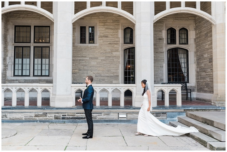 Bride walks up to groom for first look with Casa Loma as the backdrop