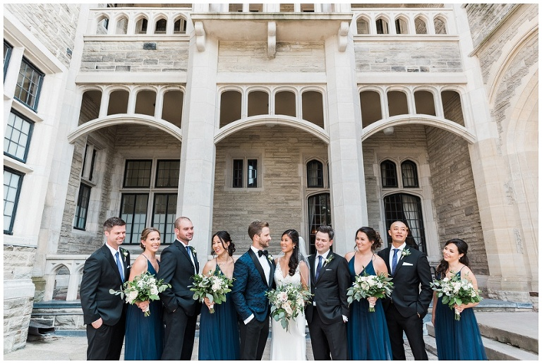 10 person wedding party looks at each other smiling and laughing for photos in front of Casa Loma