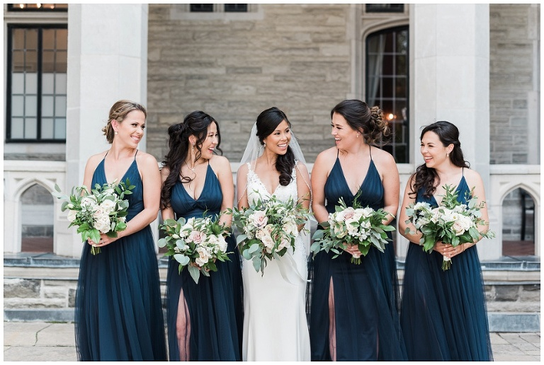 Bridesmaids laughing and holding their bouquets in front of Casa Loma