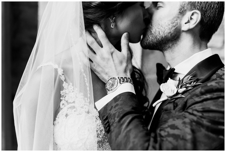 Black and white photograph of groom holding bride's neck and bringing her in for a kiss