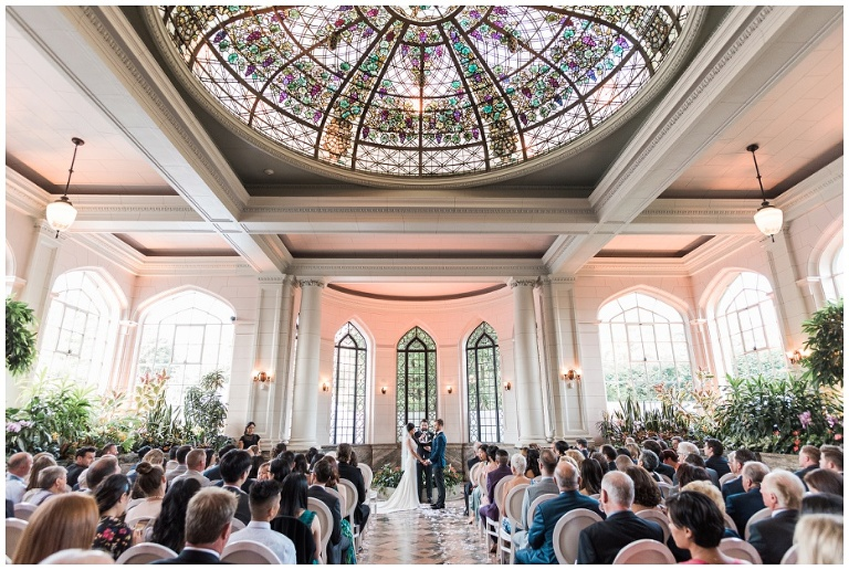Bride and groom standing at the altar getting married inside of Casa Loma ceremony space with stained glass