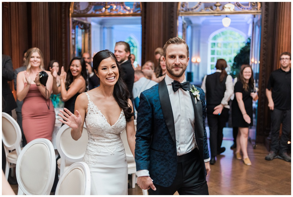 Bride and groom entering into wedding reception at Casa Loma with big smiles on their faces
