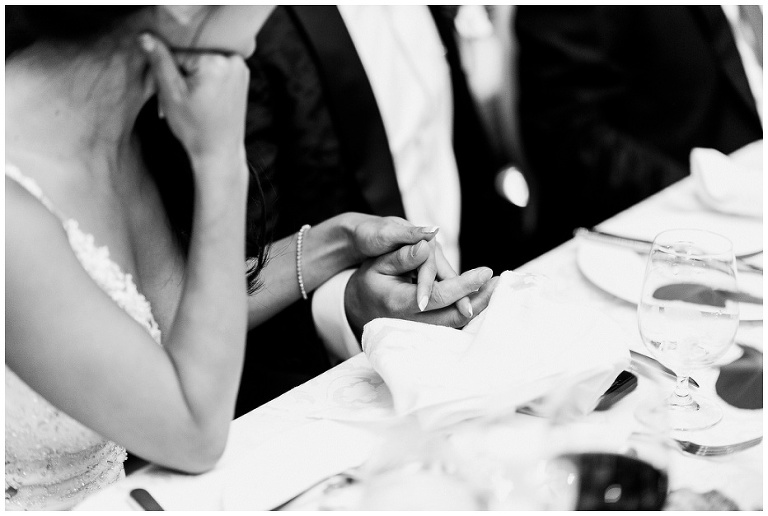 Close up in black and white of bride and groom holding hands