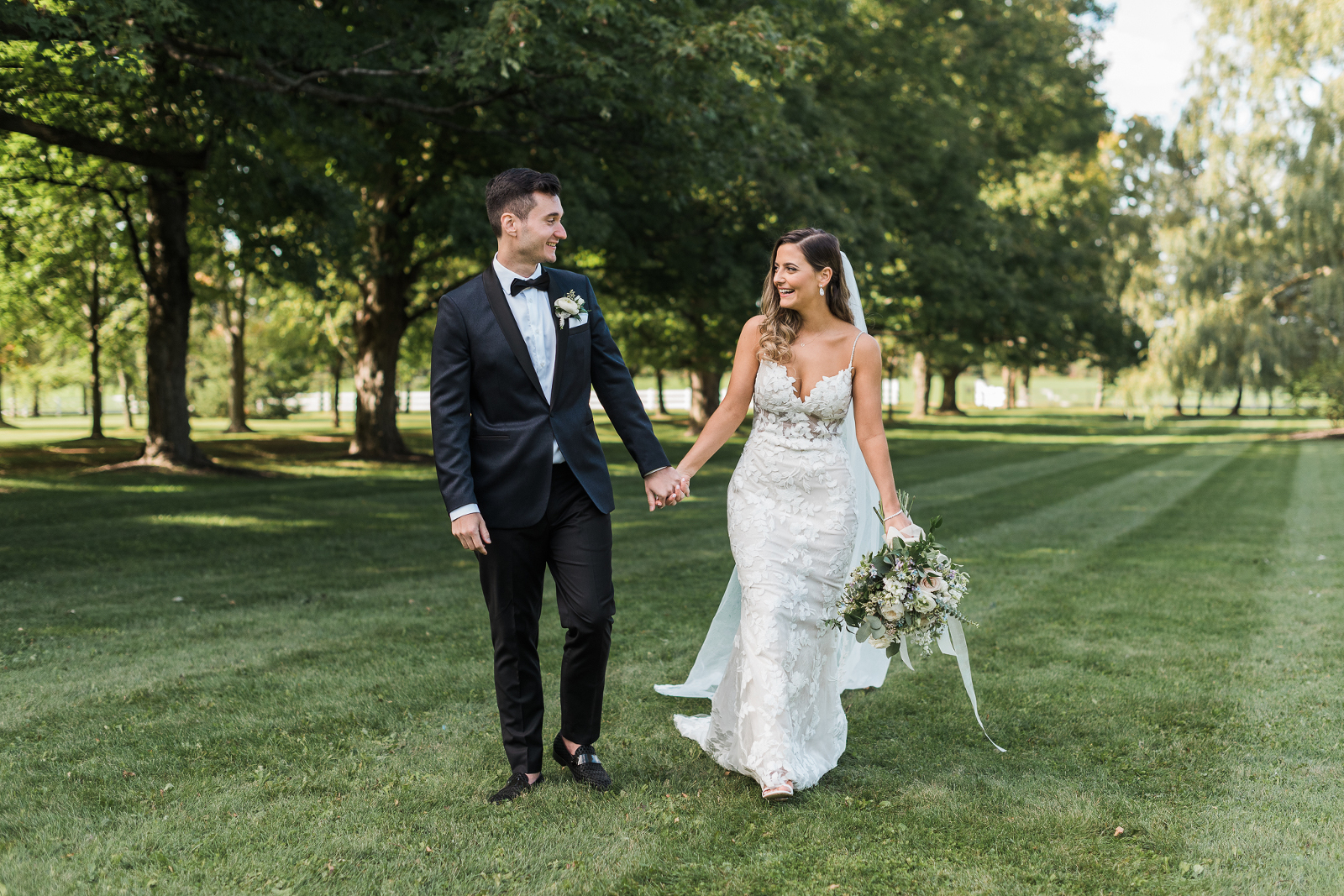 Bride and groom walking on grass at Belcroft Estates wedding venue after their ceremony