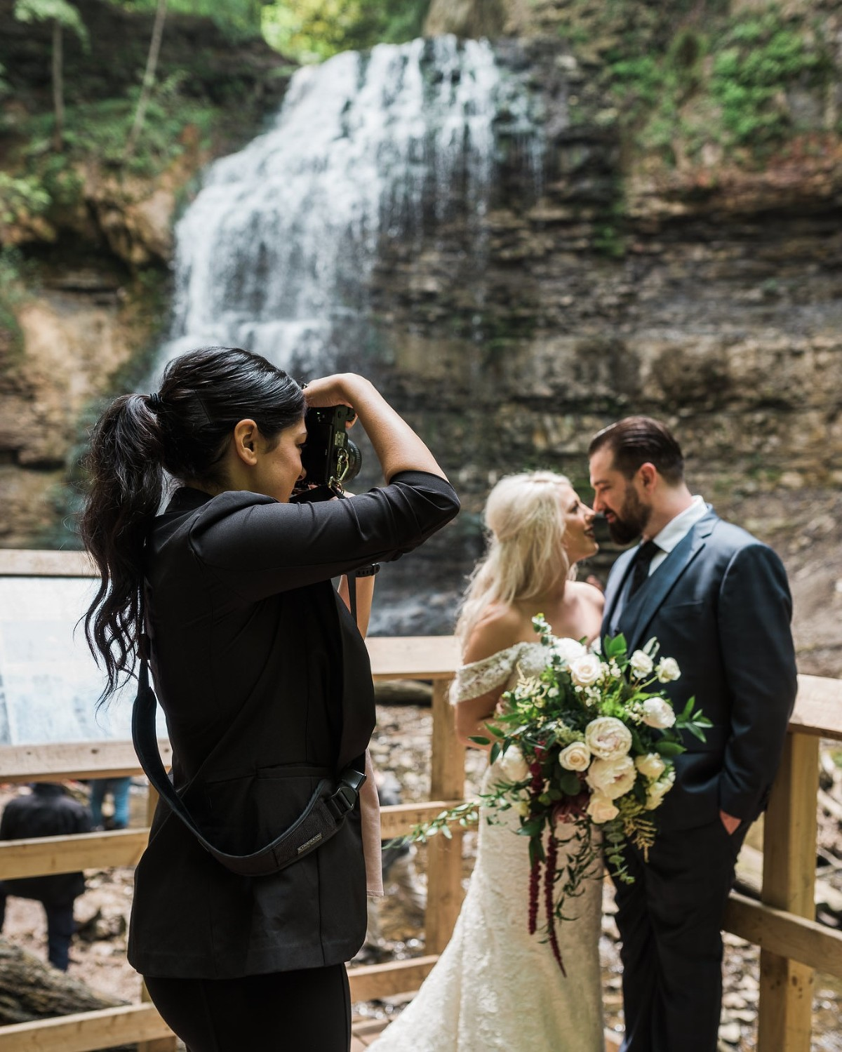 Photographer taking photo of bride and groom in front of a waterfall in Hamilton