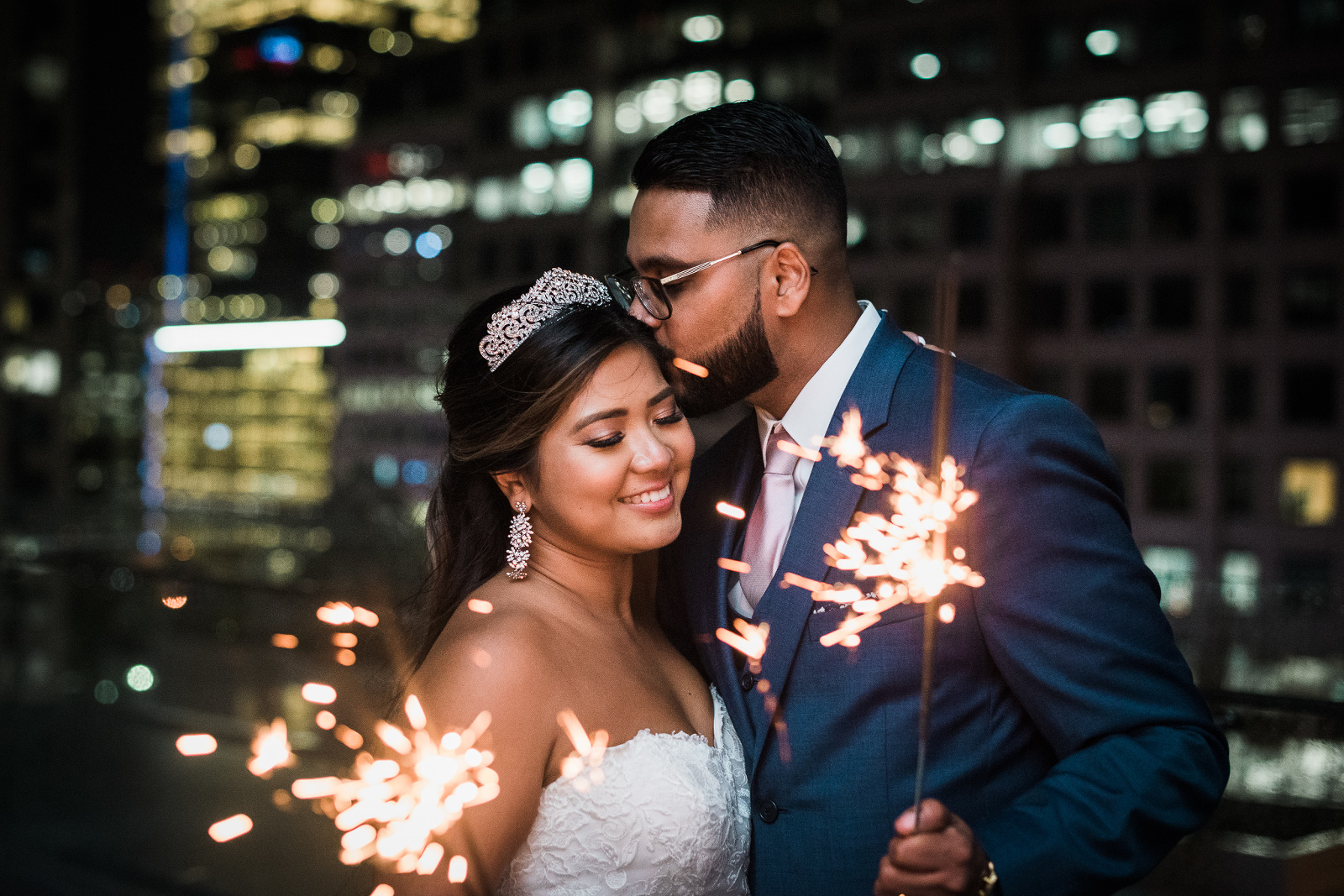 South asian bride and groom holding sparklers at night time snuggling on the rooftop of Malaparte in downtown Toronto