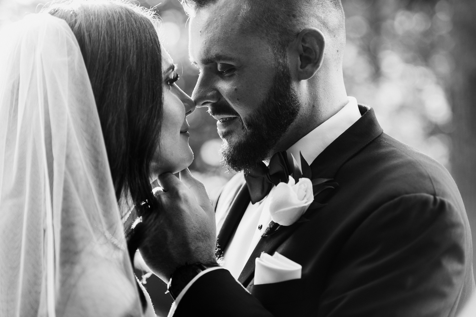 Black and white photo of groom touching bride's face to kiss at Ancaster Mill wedding